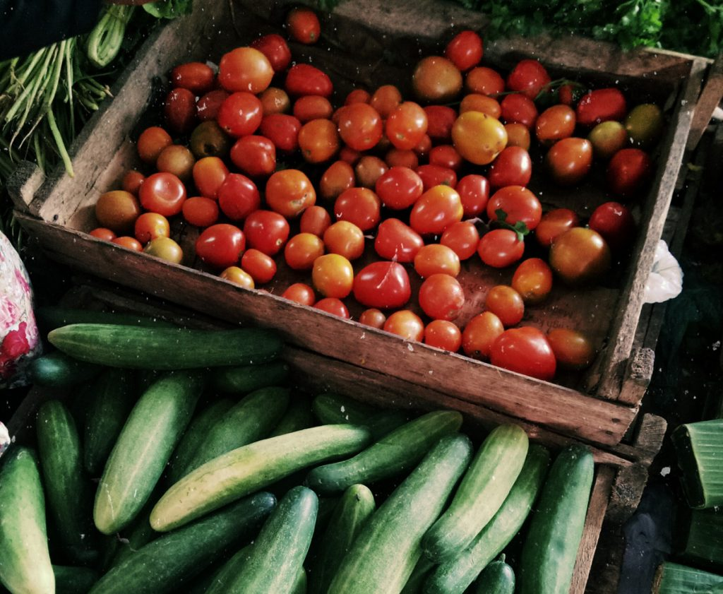 Picture of fresh cherry sized tomatoes in various reds, oranges, and yellows in a wooden crate, and cucumbers in colors from yellow to dark green piled in a wooden crate next to the tomatoes. Behind the tomato crate, some greenery is visible, which might be lettuce and herbs.